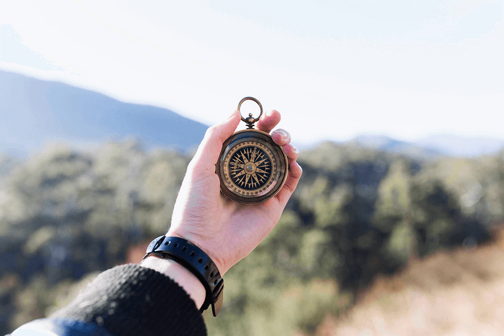 This image of a compass in the hand of a person navigating a desert reflects the difficulty of changing organizational culture without a clear strategy — if you don't know where you're heading, you'll struggle to even know which way to go.