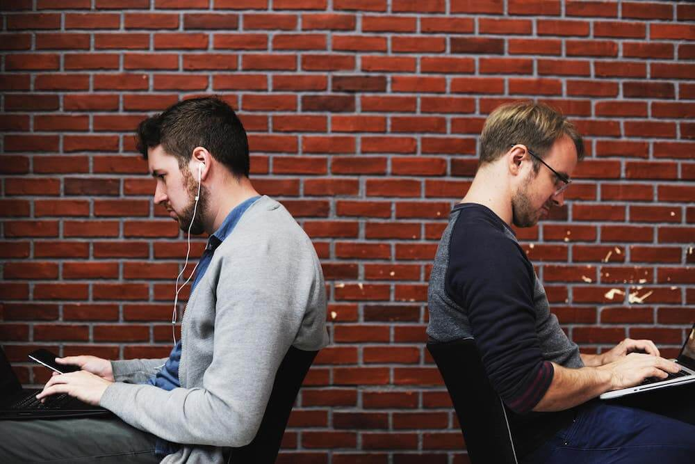 Conflict at work can turn coworkers against each other if not handled properly, as with the two men pictured, working but facing away from each other, not collaborating.