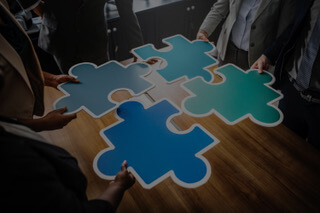 Accountability in the workplace is one of the pieces of the teamwork puzzle that ultimately improves performance — puzzle pieces ready to be put together.