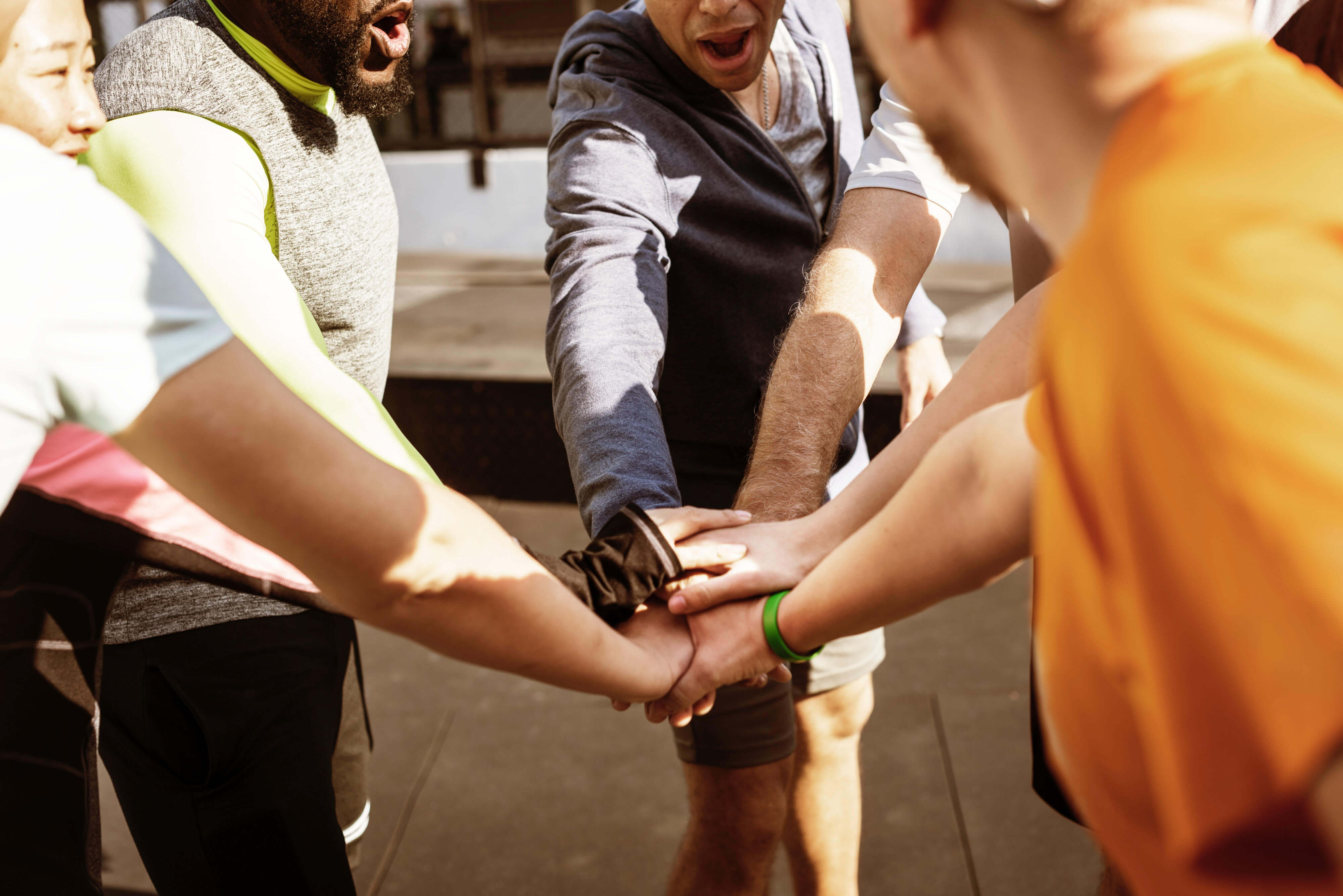 7 runners engaged in a team huddle, with arms extended and hands stacked in the middle — a suggestion for how to boost employee morale.